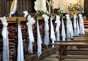 decoratie-huwelijk: witte-strikken-langs-kerkbanken
