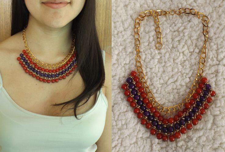 Collar con piedras de vidrio en color rojo y morado con detalles dorados.
