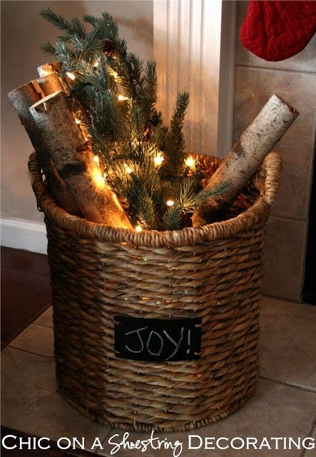 Christmas in July - lights, evergreens and logs in a basket by the fireplace