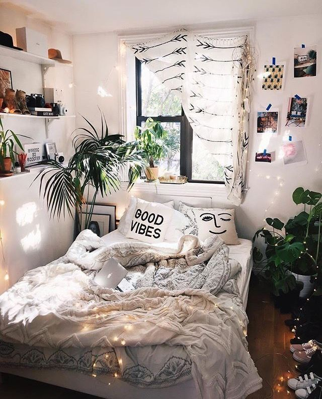 Weiße Regale und Pflanzen. Lichterketten am Kopfteil