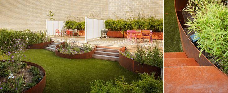 Deze stadstuin in Gent bevindt zichbovenop een parking. Wat drie kleine tuintjes zouden zijn , hebben wij dankzij de samenwerking met de buren visueel omgevormd tot één tuin. Een geheel dat meer openheid en mogelijkheden biedt. Met speelse bogen in cortenstaal zijn de tuintjes met elkaar verbonden. Ook de beplanting wordt herhaald in elke plantenbak …