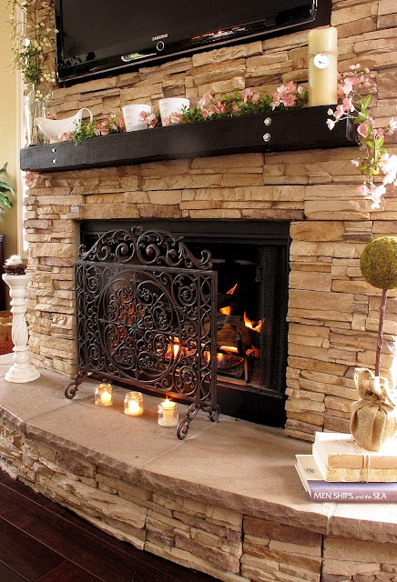 Stacked stone fireplace, iron fire screen, dark wood mantel - love it