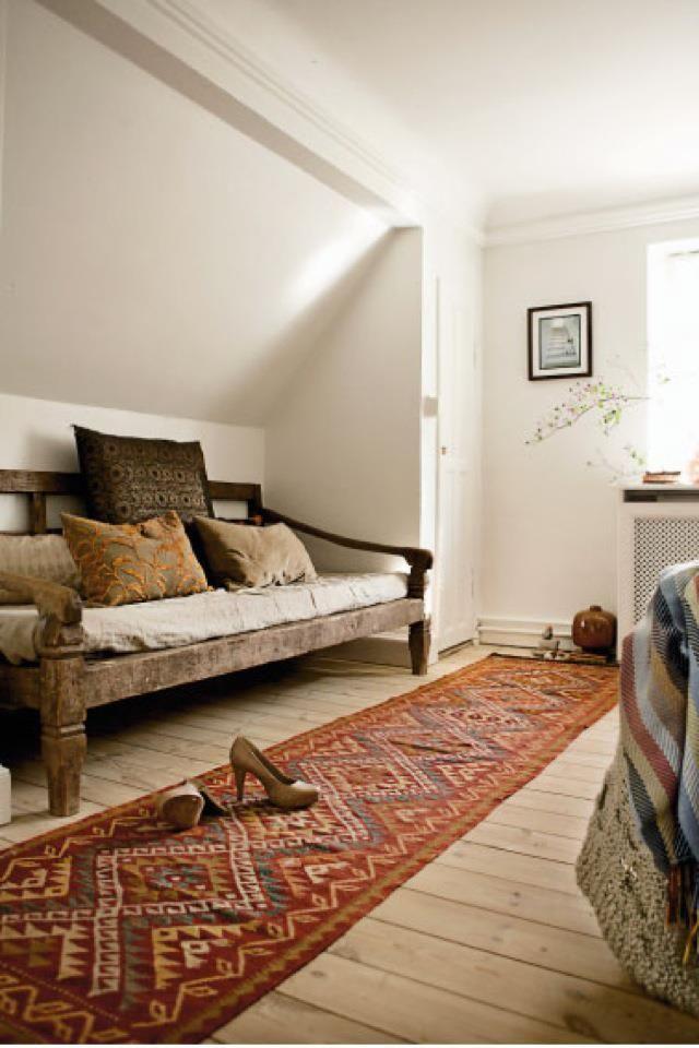 White/fresh background, natural wood bench, kelim carpet, cushions in earthy tones.