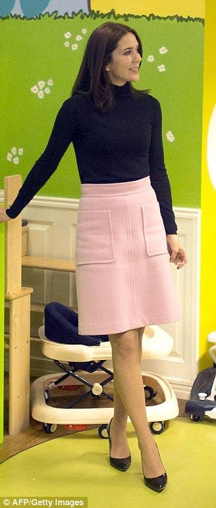 Pretty in pink: Princess Mary kept it simple with a chic pink skirt and black stilettos to visit the women's shelter Rosa Manus in November