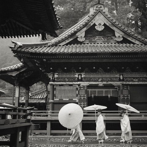 """""""Three Priests with Umbrellas at Nikko Shrine"""" Resin coated print 1947 There are many temple structures in Japan that house sacred aspects of Shintoism, but the Nikko Tosho-gu is among the most important. The architecture is very elaborate and, in the photograph, a trio of Shinto priests stroll with their parasols to protect themselves from the rain. They wear clothing characteristic to Shino priests: white robes, a black hat, and a small wooden scepter."""