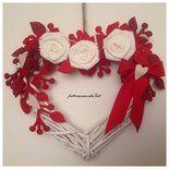 Cuore di vimini con rose di lino bianco e rametti di feltro rossi