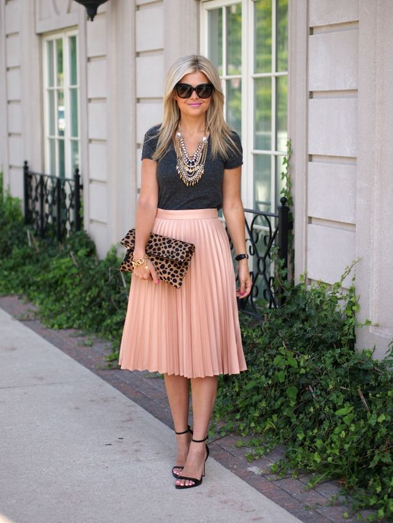 skirt with pleats worn with gray shirt and statement necklace