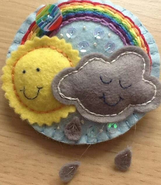 Handmade felt rainbow brooch in pale blue, with embroidery, sequins and button embellishments.