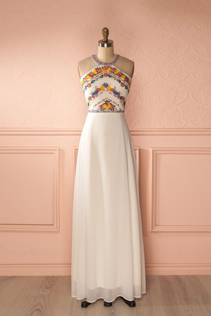 Une couronne de fleurs dans les cheveux, elle fredonnait une douce mélodie tout en marchant.  A flower crown in her hair, she hummed a sweet melody while walking. White maxi dress with embroidered halter neckline https://1861.ca/collections/products/delphonsine