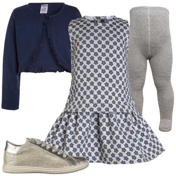 Un abito svasato al fondo, color argento, a fantasia floreale, dei collant in cotone, grigi, un cardigan blu con piccole ruches e delle scarpe in pelle color argento.