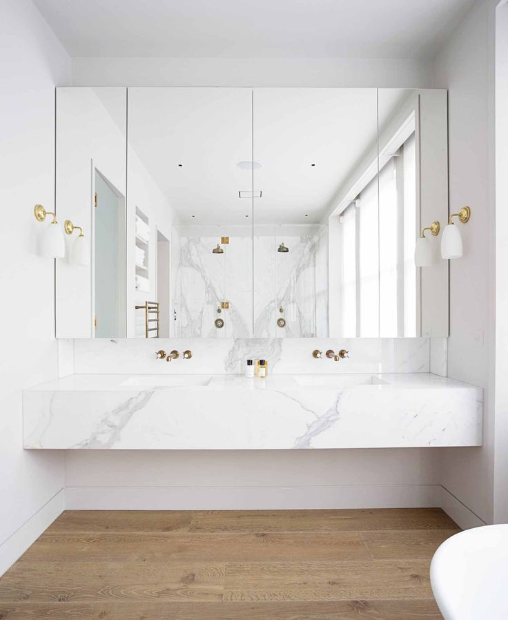 Dual white marble sinks with light hardwood flooring, large mirror, and gold fixtur