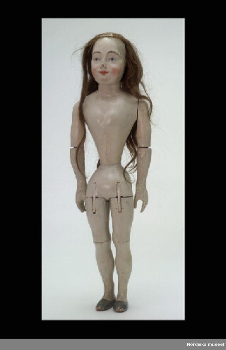 Inventering Sesam 1996-1999:  L  67  cm  Docka, damdocka av al, målad med grå oljefärg, oklädd. Skulpterat ansikte med runda kinder, målade blå ögon och skulpterade öron. Äkta långt brunt hår (möjligen senare). Formad byst, smal midja, platta fötter med målade grå skor. Axlar, armbågar, höfter och knän ledade med sprint och tapp.  Dockan är sannolikt tillverkad av en bildhuggare, ansiktet har kerubliknande drag. 1700-tal.  Birgitta Martinius 1997