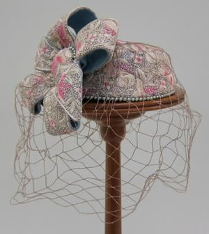 Pillbox hat of off-white and pink brocade. The conical crown with flattened top is made of brocade fabric with flowers & butterflies in off-whites, gray/greens & pinks on a grayish ground. On the right side of the hat is a large bow made of strips of the brocade backed in a gray/blue. Center of bow is encircled with a band of gray beads, with a matching band of beads at base of hat. The hat has a light tan veil. Bes-Ben / Made in Chicago