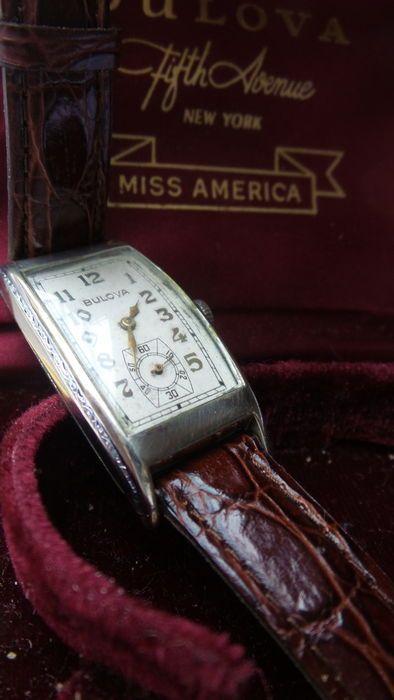 """Antique BulovaArt Deco(1930s) wit goud vergulde polshorloge in orginele Bulova box  Langwerpig(21x43mm)wit zwaar wit vergulde Art Deco polshorloge van ca.1930.Dit horloge is in een goede conditiehet heeft een lengte van onder naar boven(van lug to lug)van 43mmHet horloge loopt goedAan de zijkanten(iets onder het glas)is de kast leuk gegraveerd.Het wijzerblad is creme/lichtgrijs gekleurdzonder beschadigingen met mooie """"gouden""""Arabische cijfers en eveneens """"gouden""""wijzers(3)Verder staat op het…"""