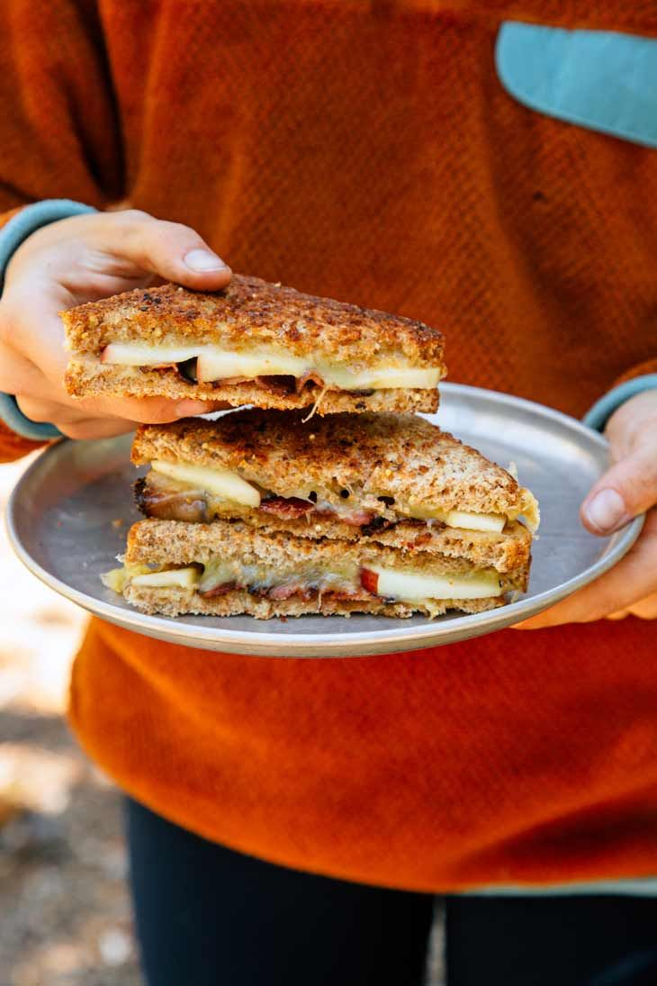Upgrade your grilled cheese game with this apple, bacon, and cheddar sandwich. Cooked in a cast iron skillet over a campfire or your camp stove, this is the quick and easy hot lunch idea you've been waiting for. Campfire cooking | Camping food #camping