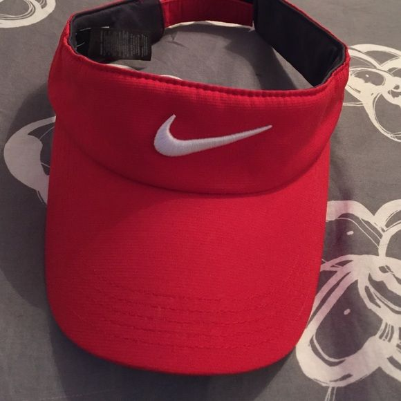 Red Nike visor Nike golf red visor. Has adjustable Velcro strap in the back. Hardly ever worn, in basically brand new condition Nike Accessories Hats