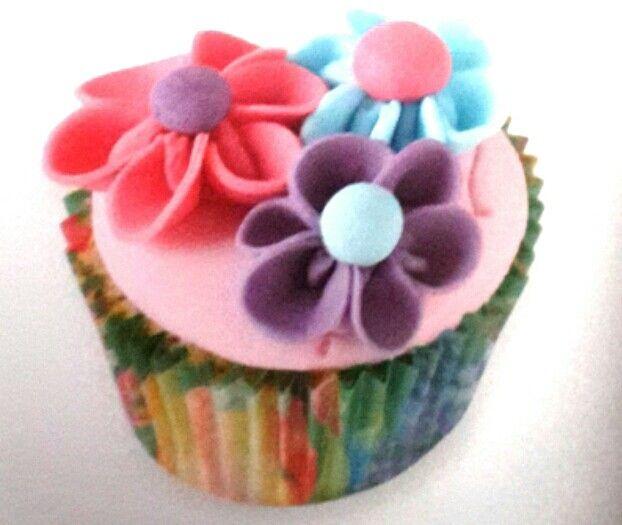 Cupcakes in pirottini colorati ricoperti di pasta di zucchero rosa con motivi floreali