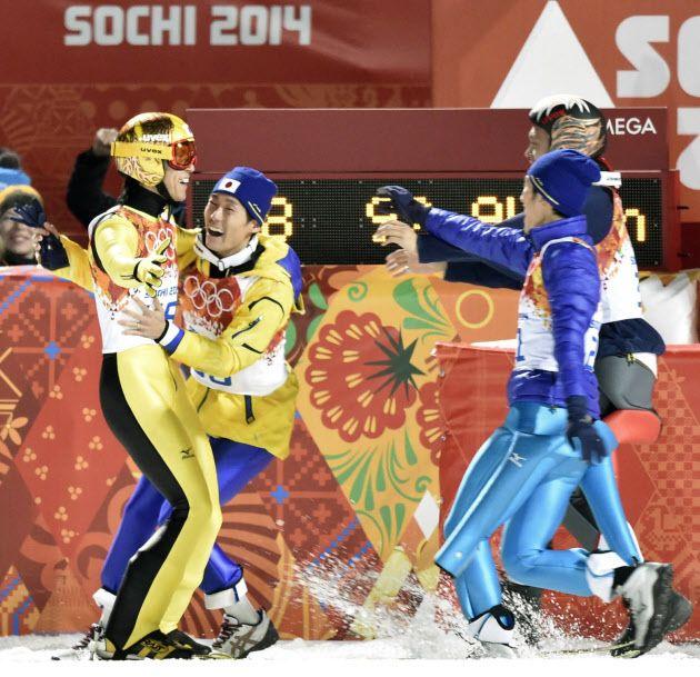 葛西(左)に駆け寄る日本選手=共同