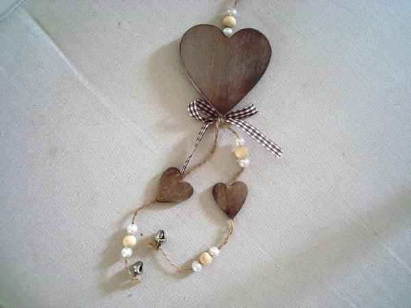 Décoration à suspendre, elle est composée de 3 coeurs en bois naturel cérusé, de deux grelots ainsi que perles, le tout est rehaussé d'un flot en tissu vichy marron et blanc. Idéal pour la déco coeur de votre intérieur. Autre modèle en blanc disponible. Dimensions: 25 cm de haut sur 7 cm de large
