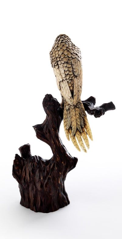 Parrot in Ivory Japan, 19th century. Carved ivory, patinated, glass, wood carved. Branches of a tree roughly carved and. On this, clinging with his claws, a preening parrot. Finely balanced portrayal of the various lots of skin and plumage. The inlaid glass eyes seem to look at the viewer.
