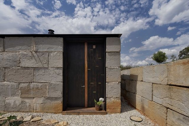 The oversized blocks of discarded concrete effectively tie the house to its site, with a solidity that timber would not have provided.