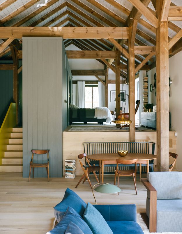 """The open living-and-bedroom area of Ian Hague's rural retreat can be divided by a wall that rises from within the master-suite platform. Interior designer Elaine Santos blended her client's collection of vintage furniture with no-fuss pieces like a Shaker-style bench by Ilse Crawford for De La Espada. <span style=""""line-height: 1.8;"""">The dining chairs are a 1959 design by Arne Hovmand-Olsen for Mogens Kold.</span>"""