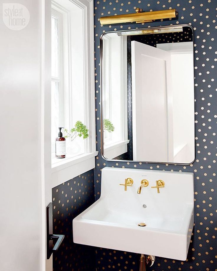 black wallpaper with gold polka dots makes for a fun powder room