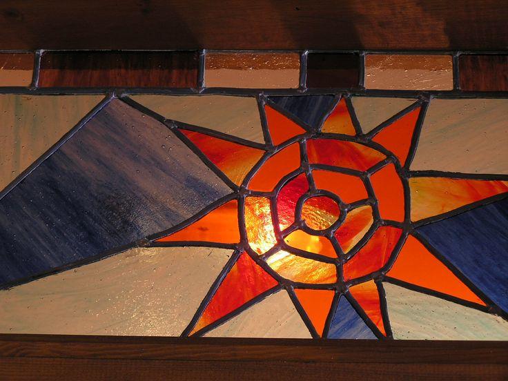 Vidriera artesana de un sol, en el alto de una puerta.