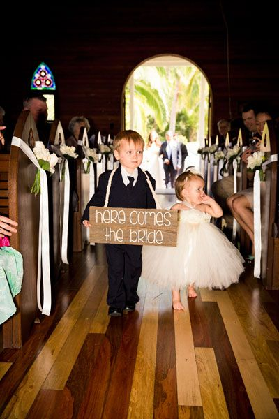 The couple's flower girl and pageboy walked down the aisle bearing a sign that read 'Here Comes the Bride'. Image: GM Photographics