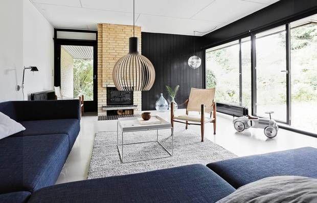 Den mørkeblå Bolia-sofa er et godt modspil til de gule mursten og den sorte trævæg. Trævæggen er ny, men passer rigtig godt ind i 70'er-arkitekturen og skaber en fin dybde og hygge i den store stue. Tæppet er fra Garant, bordet fra Hay og Safari-stolene er købt brugt. Trælampen Octo klæder 70'er- stilen. Foto: MORTEN SOBY