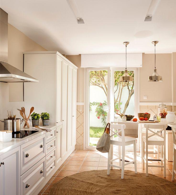 Cocina con office con muebles en blanco, suelo de toba, alfombra de fibra natural y salida al jardín