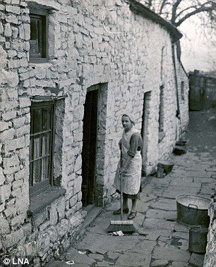 A woman sweeps outside her home in Merthyr, south Wales ...