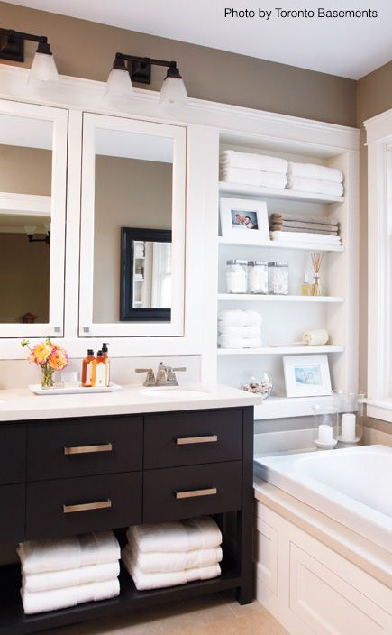Love the built-in white shelving and medicine cabinet. The dark vanity stands out with all the bright colors. Homey and transitional. Very nice. #whitebathroom