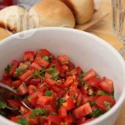 Ensalada de tomates: 3 tomates en cubitos,1 ají rojo, picado, 1/2 cebolla morada, cilantro picado, aceite y limón a gusto * colocar los tomates picados, y el ají. En otro bowl, colocar la cebolla morada y cubrir con agua hirviendo de la pava. Dejar reposar 5 minutos y colar. Enjuagar con agua de la canilla y agregar a la ensaladera. Salpicar todo con cilantro. Preparar un aderezo con sal, aceite y jugo de limón a gusto. Rociar sobre la ensalada y servir.
