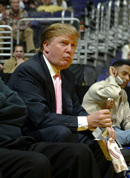 real estate tycon and reality television personality Donald Trump eats a Ben and Jerry's ice cream bar as he watches the Los Angeles Lakers game...