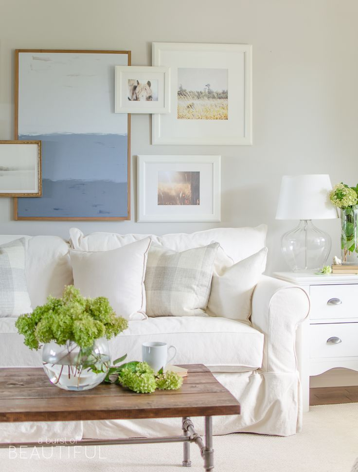 A white slipcovered sofa creates a casual and relaxed feel in this modern…