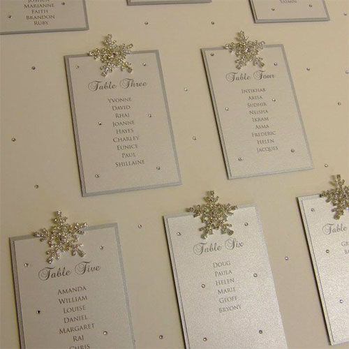 Beautiful crystal snowflake winter wonderland wedding table plan in silver and white.