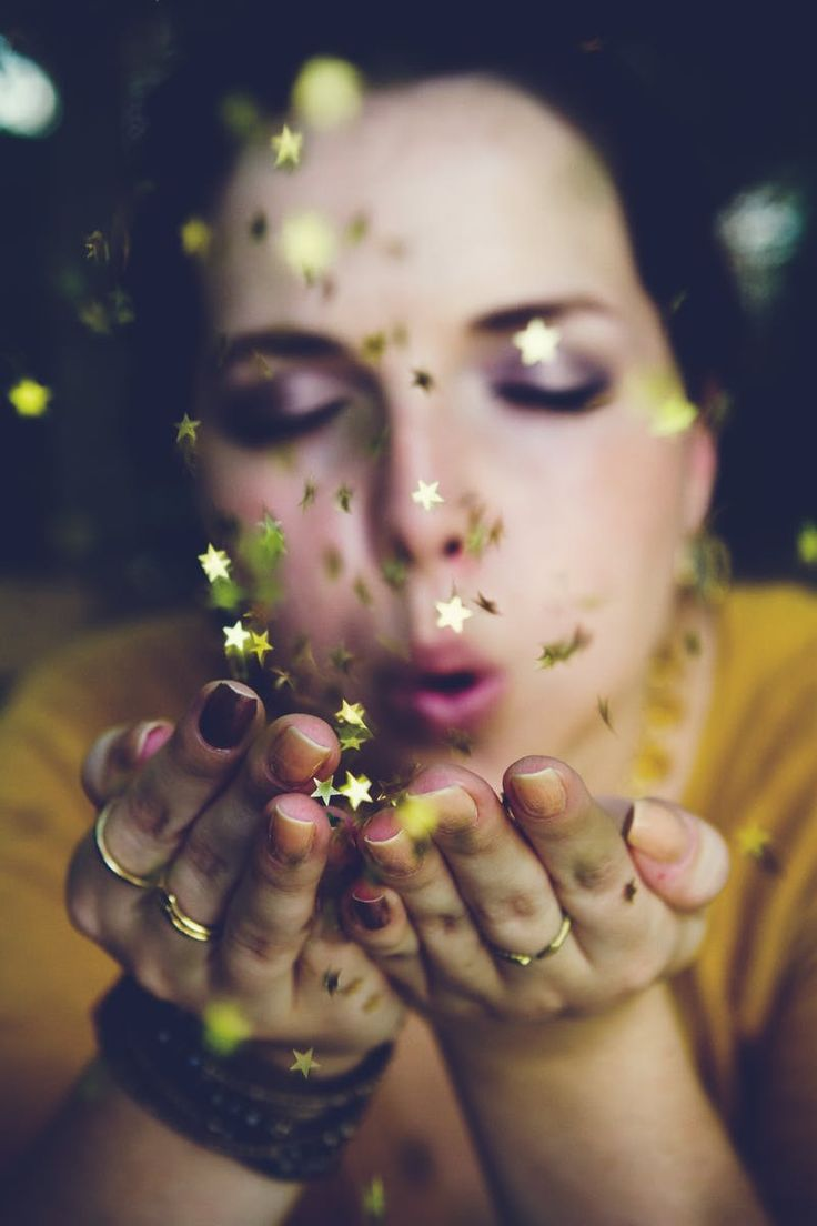 Woman in Yellow Shirt Blowing a Gold Star Glitter