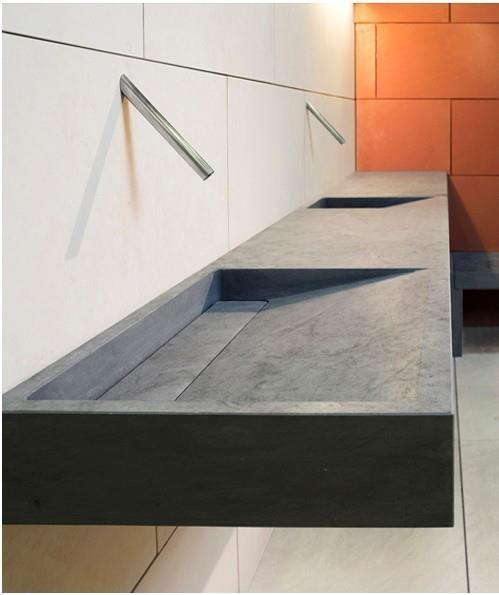 Moderne betonnen wastafel waar de kranen in de muur zijn weggewerkt.