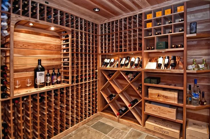 Rustic Wine Cellar with slate tile floors, Built-in bookshelf, Designer series 95-bottle 5-column wine rack with display row