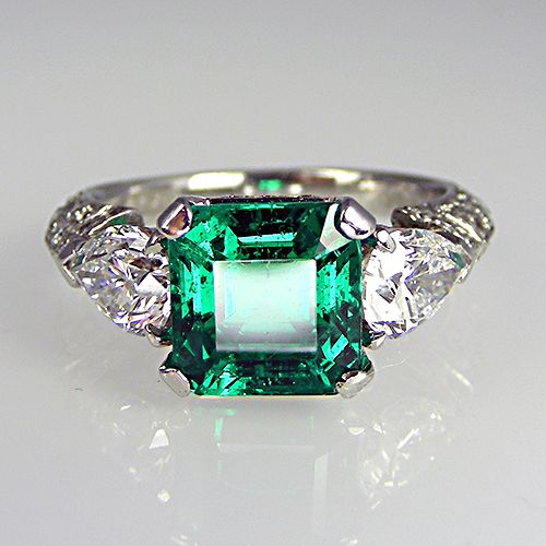 Old mine, Columbian gem quality emerald ring in platinum with pear shape diamonds either side and pave set diamond collet and shoulders. Eme...