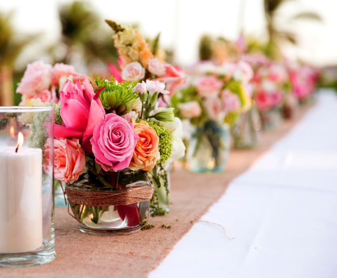 Roses get the modern beach treatment in these bright mixed floral arrangements at a Grand Hyatt Bali wedding.
