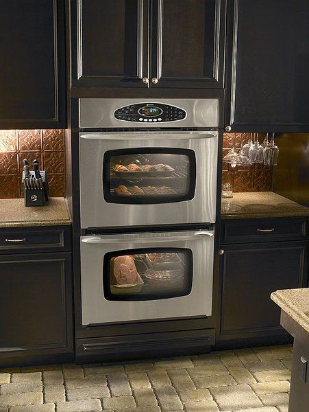 love the travertine marble floor black cabinets double wall oven and copper backsplash