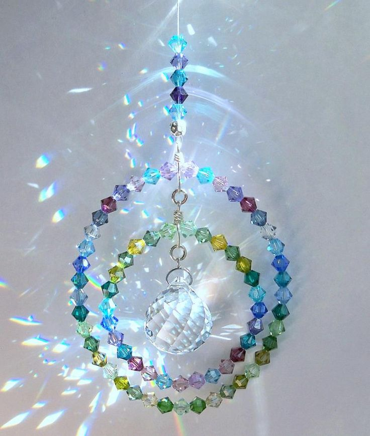 """This unique suncatcher is reminiscent of warm, still nights, rockin' on the porch, listenin' to a frog on a Lily Pad.   I created this suncatcher with 74 5mm Swarovski Bicone crystals in shades of Lilac, Lavender, Blues and Greens.  The outer circle measures approximately 2 1/2"""" and the inner circle swings freely as you can see in my photos.  The center crystal is an exquisite 20mm Swarovski Strass faceted Crystal Ball.  The entire length of the suncatcher, including the pla..."""