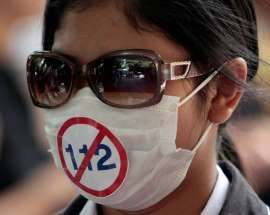 In this May 11, 2011, a protester wears a mask with a sticker against the Thai Criminal Code 112, which prohibits people from defaming the monarchy, at a police station in Bangkok, Thailand.