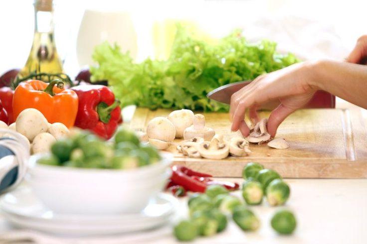 Mujer cortando champiñones y otras verduras