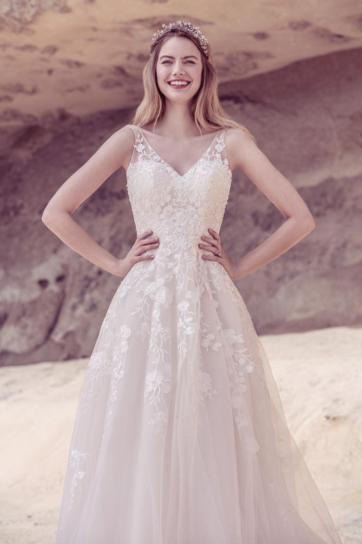 - STYLE 18041 - Romance in bloom. Cascades of soft tulle falls from the waist, decorated with soft ribbon. The embroidered vines entwine with soft flowers the length of the dress, punctuated by stunning beaded highlights. The A-line shape is soft and flattering, allowing the detail to take centre stage. #EllisBridals #WeddingDress #Bridal