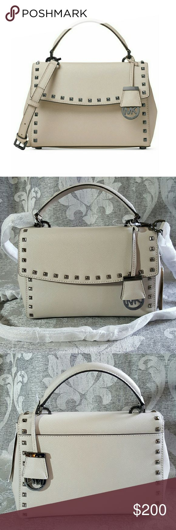 "Michael Kors Ava Small Satchel NEW Michael Kors Ava Small Top Handle Satchel in Cement!	Petite pyramid studs add an edgy element this compact top handle satchel. Has a strap to make it a crossbody! PRICE FIRM. LESS ON Ⓜerc  Saffiano leather; lining: polyester Small sized bag; 12""W x 7""H x 3-3/4""D Interior features lining, 1 zip pocket and 1 open pocket 4""L top handle; 21"" to 24""L adjustable strap Magnetic snap closure Exterior features shiny rhodium-tone hardware, studded detail and 1 back…"