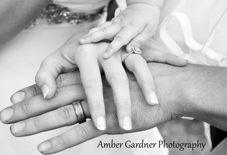 Hands of the bride, the groom, and their daughter. Wedding photography by Amber…