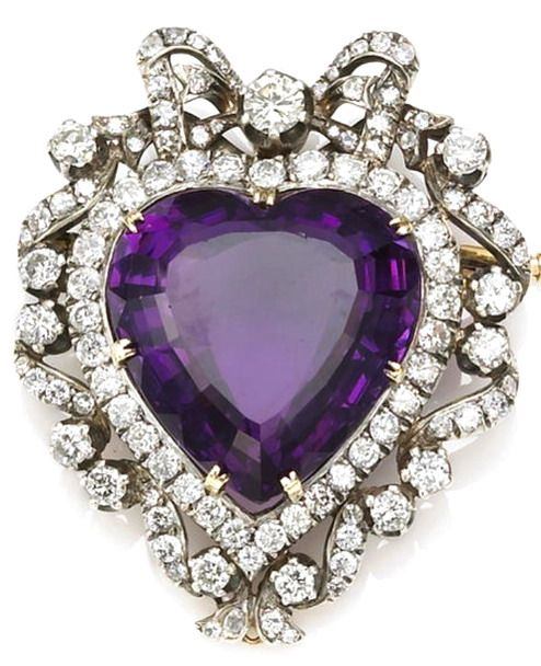 An amethyst and diamond brooch-pendant centering a heart-shaped amethyst; estimated total diamond weight: 4.20 carats; mounted in silver-topped eighteen karat gold; dimensions: 2 x 1 1/2 x 11/17in.